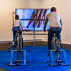 """Two people riding bicycles as part of Eugenia Lim's artwork """"On Demand"""""""