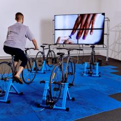 Person cycling in front of a screen